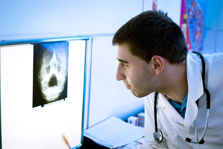 Young doctor taking look at x-ray image on the wall. photo