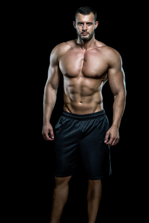 Young adult man standing in gym and posing. Banque d'images