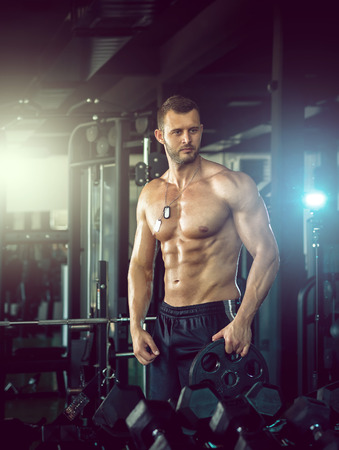 Young adult man posing in gym
