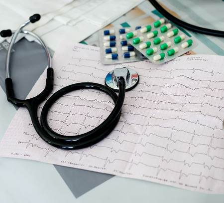 Stethoscope, pills and ECG chart on desk photo