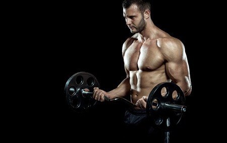 man lifting weights: Man doing weight lifting in gym on black background. Stock Photo