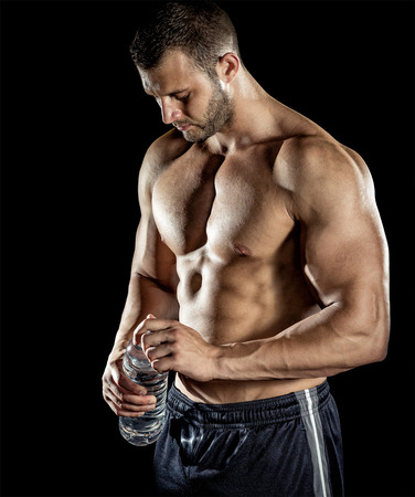 Young adult man drinking water in gym. photo