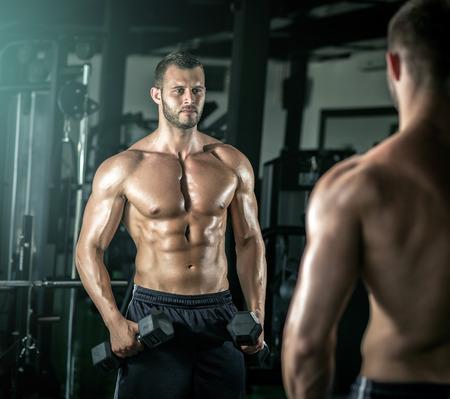 Junge Erwachsene Mann tun Bizeps Locken in modernen Fitnessraum.