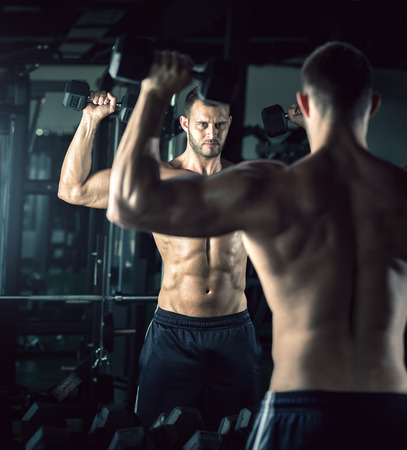 arms body: Young adult man doing bicep curls in modern gym.