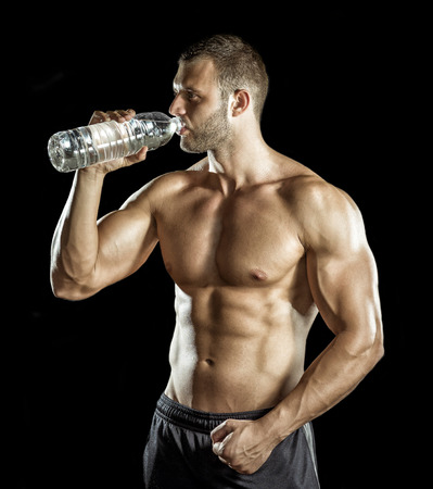 Young adult man drinking water in gym.