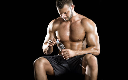man drinking water: Young adult man drinking water and sitting on gym ball.