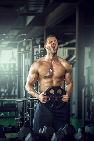 Young adult bodybuilder screaming in gym. photo