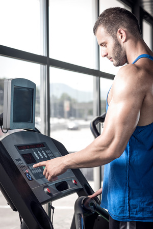 control panel: Young adult man setting control panel of treadmill before doing exercise. Stock Photo