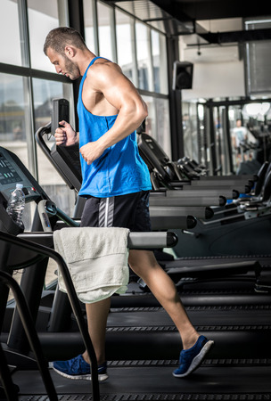 healthy body: Young adult man running on treadmill in gym Stock Photo