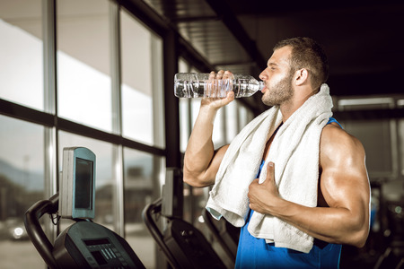 Young adult man drinking bottle of water on threadmill in gym.