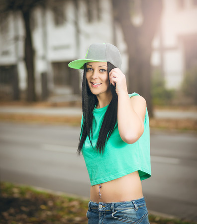 belly button: Young adult female standing outside and posing with pierced belly button.