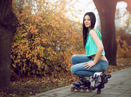 Young adult girl kneeling on roller skates in park during autumn season. photo