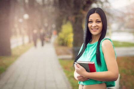 Young adult girl holding book in park photo