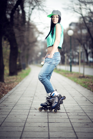 Young adult teenage girl doing roller skating in park during winter photo