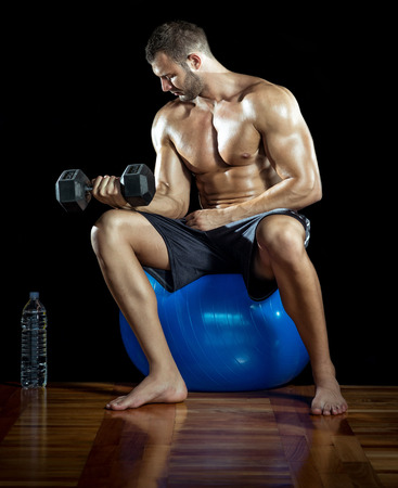 Man doing bicep curls while sitting on gym ball photo