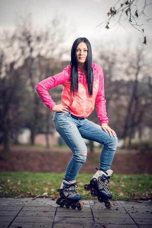 belly button girl: Young adult teenage girl doing roller skating in park during winter Stock Photo