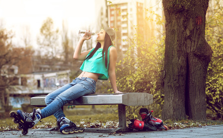 Young adult girl with roller blades drinking bottled water whlie relaxing on bench.