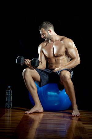 Young adult man sittin on blue gymnasium ball and doing bicep curls. photo