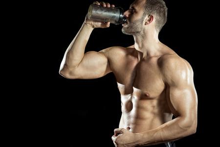 белки: Молодой взрослый человек, пить протеиновый коктейль в тренажерном зале. Черный фон.