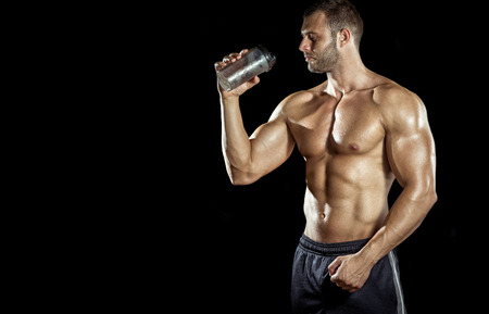 белки: Young adult man drinking protein shake in gym. Black background.