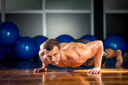Young adult man doing push-ups in gym. Stock Photo