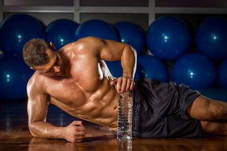 sport hall: Young adult bodybuilder taking relax lying on gym floor. Stock Photo