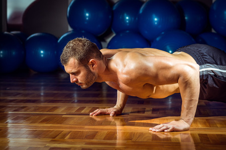 Young adult man doing push-ups in gym. photo