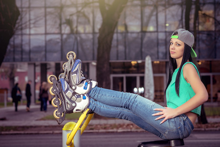 Young adult girl relaxing on open air gym fitness machine with legs up. photo