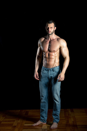 topless jeans: Man posing wearing jeans in front of black backgroud
