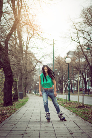 Young adult teenage girl doing roller skating in park during winter Stock Photo
