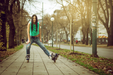 sexy teenage girls: Young adult teenage girl doing roller skating in park during winter Stock Photo