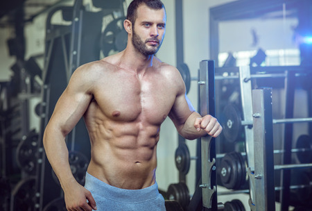 Man posing in gym and showing abs