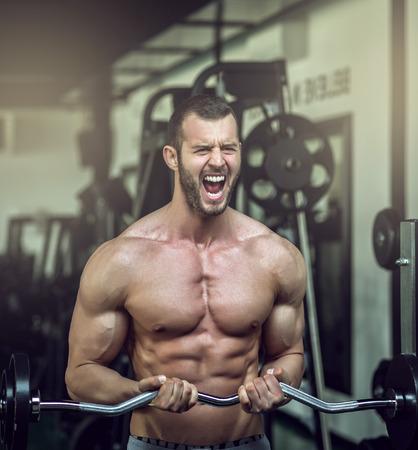 levantar pesas: Culturista adulto joven que hace el levantamiento de peso en el gimnasio, mientras gritaban Foto de archivo