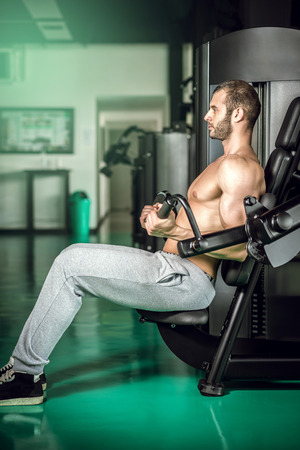 tricep: Man working out at biceps curl machine