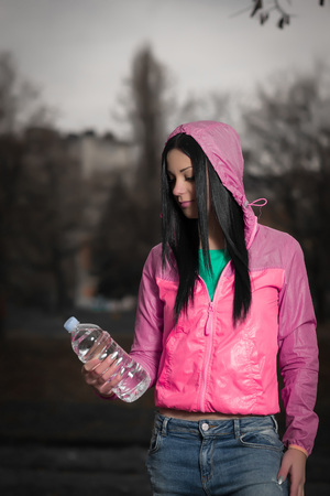 belly button girl: Young adult girl holding a bottle of water in hand outdoor. Stock Photo