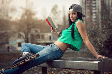 Young adult girl sitting in park on bench and reading a book. photo