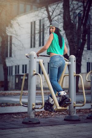 trabalhar fora: Jovens adultos ajuste menina que faz a aptid�o exercitar-se no gin�sio M�quina de p�blico.