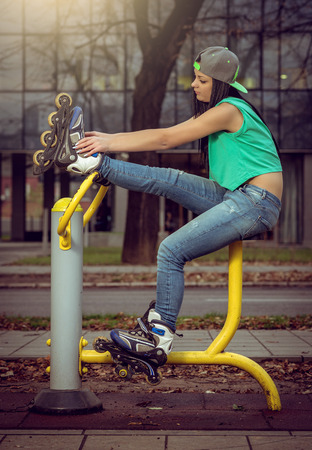 legs open: Young adult girl relaxing on open air gym fitness machine with legs up.