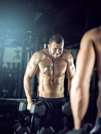 curls: Young adult man doing bicep curls and posing in gym