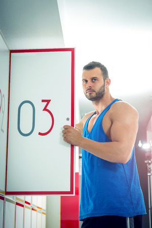 Young adult man opens locker door in gym with number three and standing there. photo