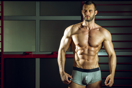 Young adult man posing in pants in gym