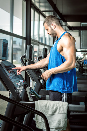 Young adult man setting control panel of treadmill before doing exercise. Stock Photo