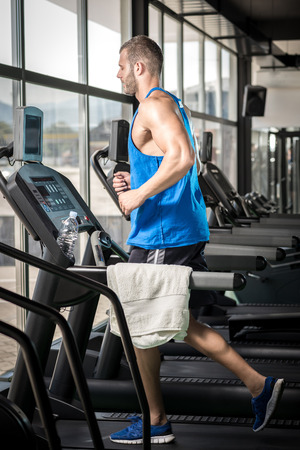 Young adult man running on treadmill in gym Stock Photo