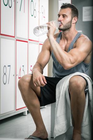 Junge erwachsene müde Mann Trinkwasser im Umkleideraum der Turnhalle.