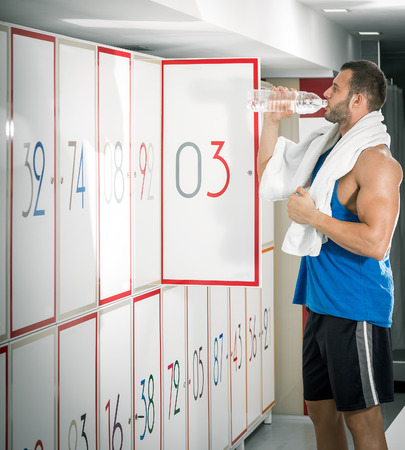 locker room: Young fit adult man drinking water in locker room of gym facility.