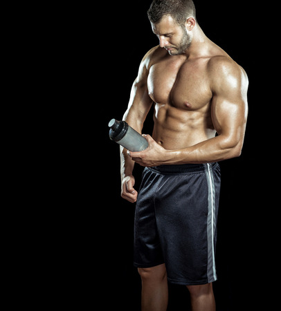 male bodybuilder: Young adult man drinking protein shake in gym. Black background.