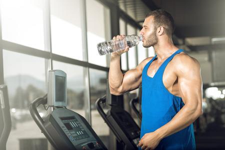 若い成人男性がジムで threadmill に水のボトルを飲みます。