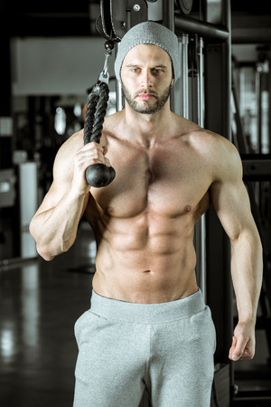 arms body: Young adult bodybuilder doing triceps overhead extension rope exercise Stock Photo