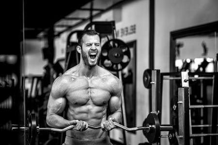 Junge erwachsene Bodybuilder tun Gewichtheben in Fitness-Studio, während schreien