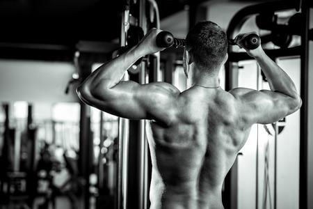 Junge Erwachsene Bodybuilder tun Klimmzüge in Fitness-Studio. Standard-Bild